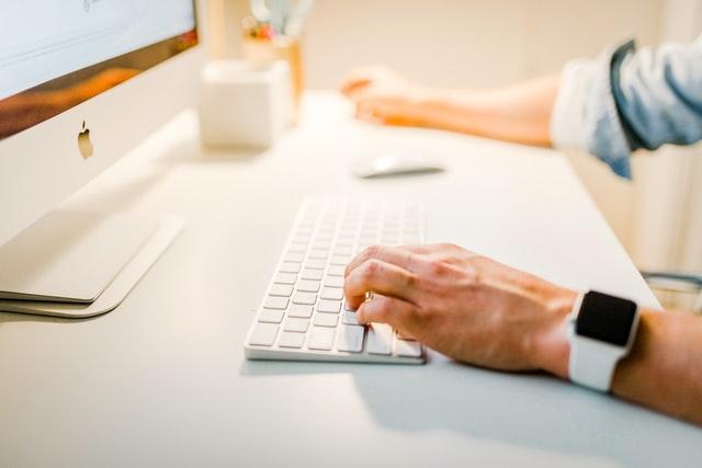 Mann schreibt am PC