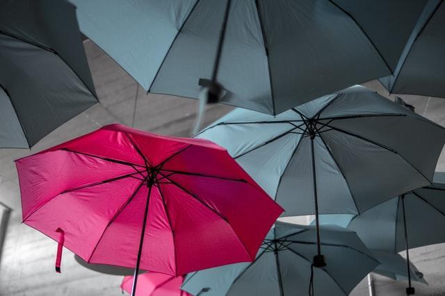 zeigt einen bunten unter lauter grauen Schirmen (USP)